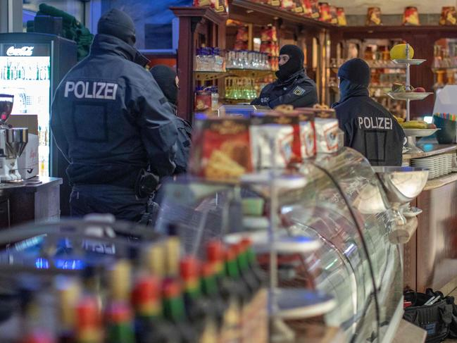 Policemen raid a cafe in Germany, as part of a mafia crackdown. Picture: AFP