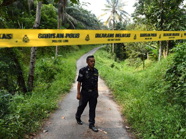 A policeman walks near a police line at an entrance to the Dusun Resort. Picture: Mohd Rasfan/AFP