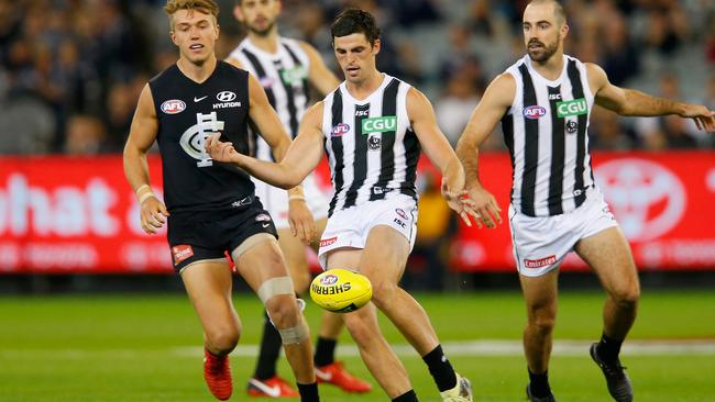 Scott Pendlebury kicks in front of Patrick Cripps.