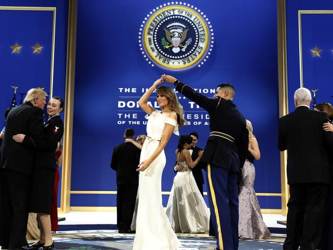 President Donald Trump, left, dances with Navy Petty Officer 2nd Class Catherine Cartmell as first lady Melania Trump is spun by Army Staff Sgt. Jose A. Medina during a dance at their third and final ball.