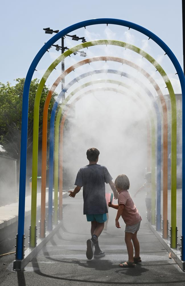 Children walk through a mist tunnel to cool at the Australian Open tennis. Picture: Saeed Khan/AFP