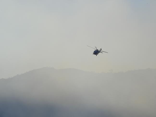 A firefighting helicopter flies through the smoke in Calabasas. Picture: AFP