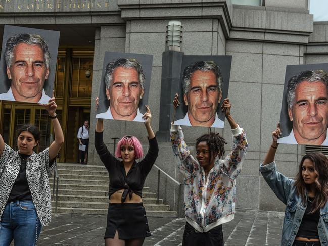 "A protest group called ""Hot Mess"" hold up photos of Jeffrey Epstein in front of the Federal courthouse in New York City. Picture: AFP"