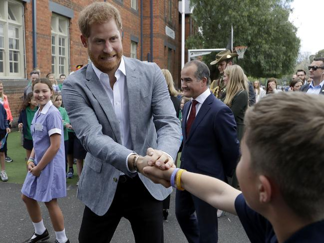 Let go, buddy! Prince Harry has a moment with a boy at the school. Picture: Kirsty Wigglesworth