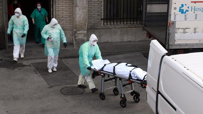 A health worker carries a body on a stretcher outside Gregorio Maranon hospital in Madrid. Picture: AFP