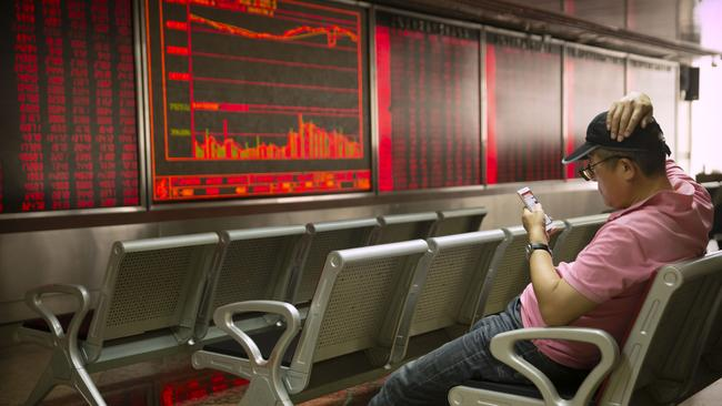 A Chinese investor uses his smartphone as he monitors stock prices at a brokerage house in Beijing on Friday, May 10, 2019. Picture: Mark Schiefelbein/AP