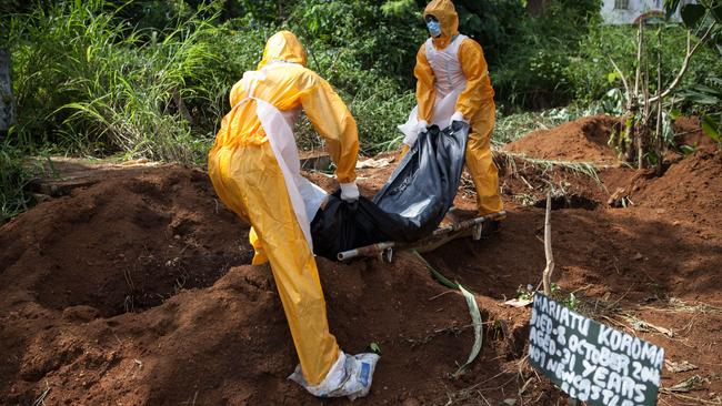 A team of funeral agents specialised in the burial of victims of the Ebola virus put another body in a grave. (AFP PHOTO FLORIAN PLAUCHEUR)