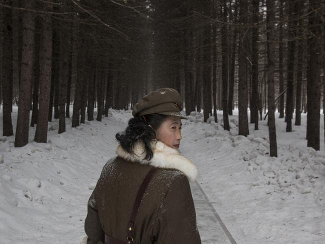 A North Korean soldier walks through a forest said to be a former camp site where Kim Il Sung stayed overnight while leading a battle against the Japanese.