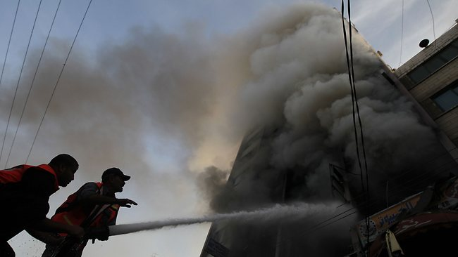 Palestinian firefighters extinguish a blaze following an Israeli air strike on the Gaza City tower housing Palestinian and international media. Picture: AFP