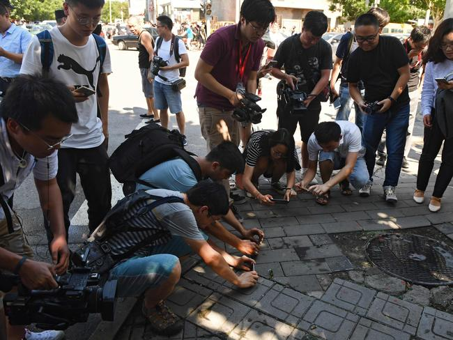 Journalists take photos of scattered glass and blood on the pavement outside the US embassy compound in Beijing. Picture: AFP