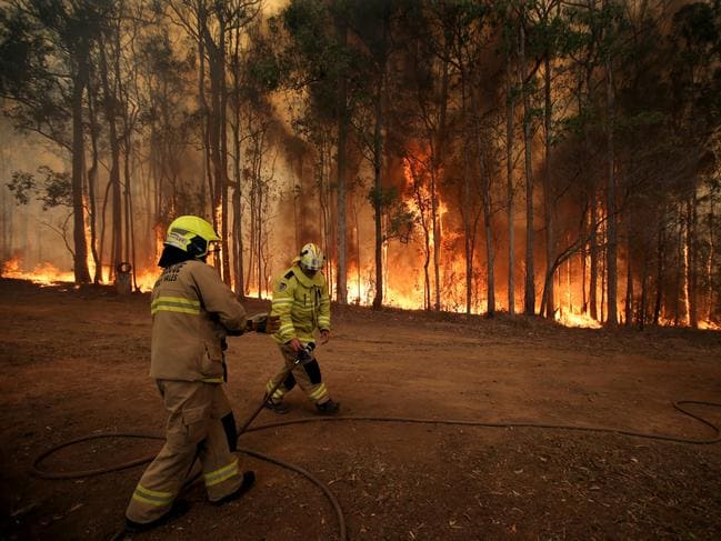 Firefighters hold back a fire threatening a house on The Buckets Way at Tinonee near Taree on the NSW mid north coast. Picture: Nathan Edwards