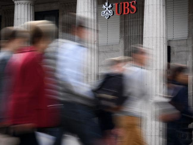 People cross a road past a sign of Swiss banking giant UBS hanging outside a branch in Lausanne. Picture: AFP