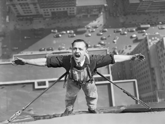 March 24, 1936: Ahh-h-h! One of the intrepid window washers working on the Empire State Building, as he pauses in his task to draw a lung-full of clean air at his height. Picture: Bettmann/CORBIS