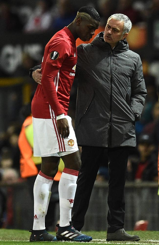 Manchester United's French midfielder Paul Pogba (L) talks with Jose Mourinho.
