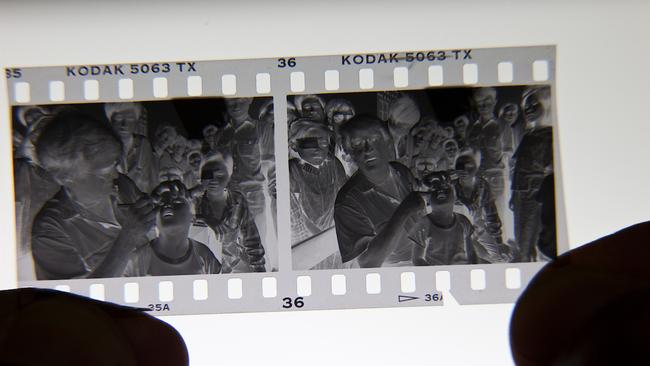 A technique news photographers once used in editing the punch hole in the bottom of the negative of the image chosen for printing and transmitting back to Australia for the original story. Picture: Michael Amendolia