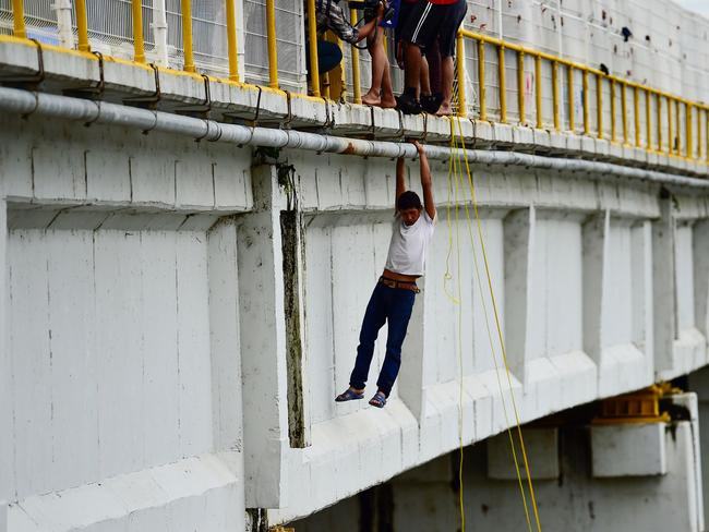 A Honduran migrant prepares to jump to the Suchiate River from the Guatemala-Mexico international border bridge in Mexico, on October 20, 2018. Picture: AFP