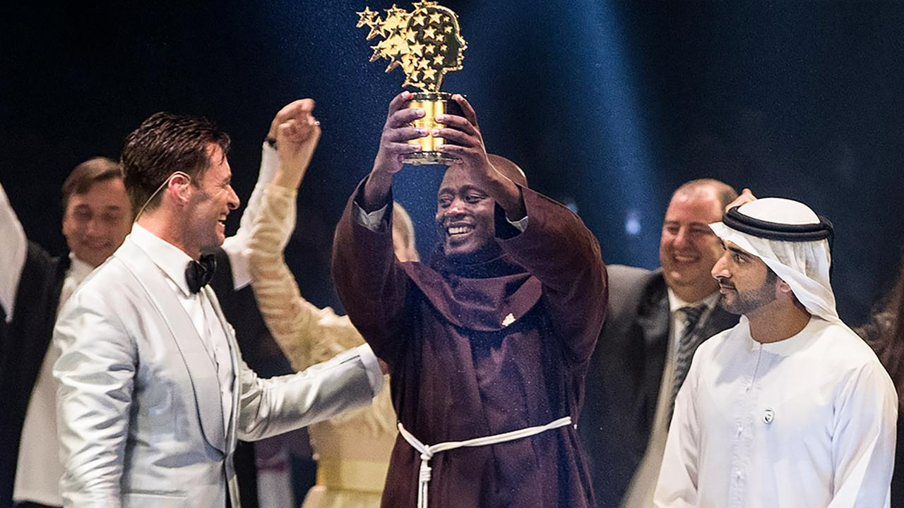Kenyan teacher Peter Tabichi (centre) holding up the Global Teacher Prize trophy presented by Australian actor Hugh Jackman (left) and attended by the Dubai Crown Prince Hamdan bin Mohammed Al Maktoum (right). Picture: AFP/Global Education and Skills Forum