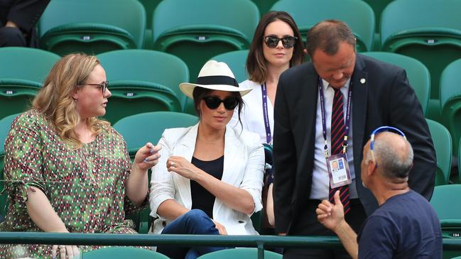 A man believed to be a Royal bodyguard had a stern chat with a spectator who had taken a selfie as the Duchess of Sussex watched the Serena Williams match at the Wimbledon Championships. Picture: Mike Egerton/PA Wire.