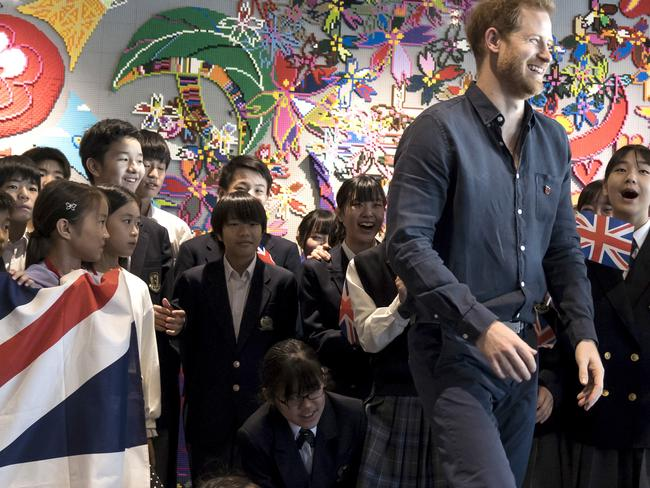 Britain's Prince Harry leaves a photo session with students as he visits the Nippon Foundation Para Arena in Tokyo. Picture: AP