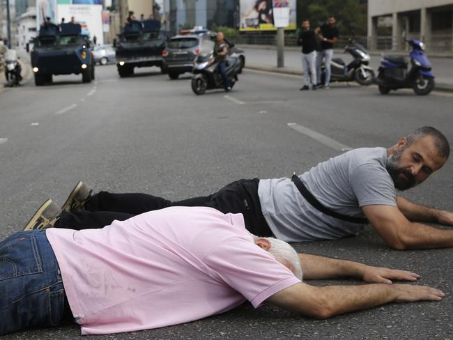 Anti-government protesters lie on the ground as they block a main highway. Picture: AP Photo/Hussein Malla