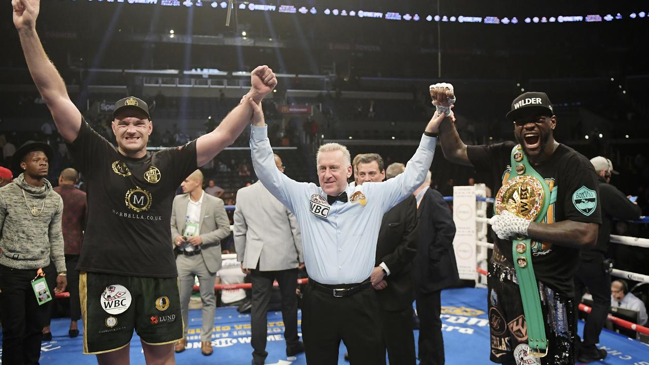 Tyson Fury, left, of England, poses with Deontay Wilder, right, along with referee Jack Reiss after their WBC heavyweight championship match.