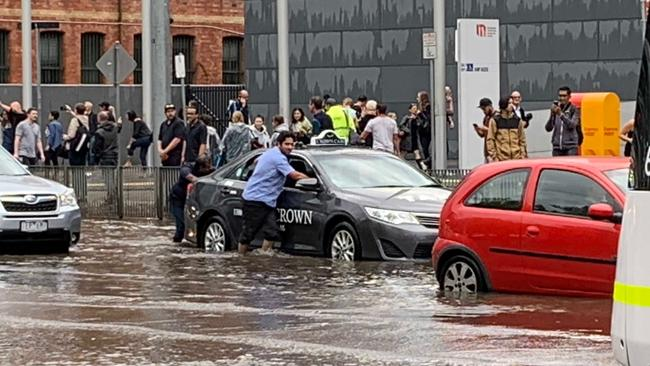 A taxi driver pushes his car through floodwater on Clarendon St in South Melbourne. Picture: Craig Hughes