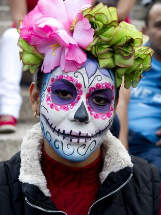 A painted woman poses before taking part in a march in Mexico City. Picture: AFP/ Yuri CORTEZ