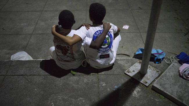 Boys embrace on as they take a time-out from their Copeira class, assigned to them as a punishment for arguing, at a community centre in the City of God slum in Rio de Janeiro, Brazil. Picture: AP Photo/Leo Correa