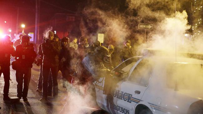 Outrage ... a protester throws a smoke device at a police vehicle in Ferguson. Picture: AP Photo/David Goldman