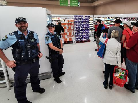 Police Officer watch as people queue for a delivery of toilet paper, paper towel and pasta at Coles Supermarket, Epping in Sydney, Friday, March 20, 2020. Supermarkets have been struggling to keep up with demand for products such as toilet paper in recent days, as panic buying as a result of the Covid-19 pandemic has resulted in people purchasing far more than usual. Supermarkets have put in place limits on the quantity people can purchase of many everyday items. (AAP Image/James Gourley) NO ARCHIVING
