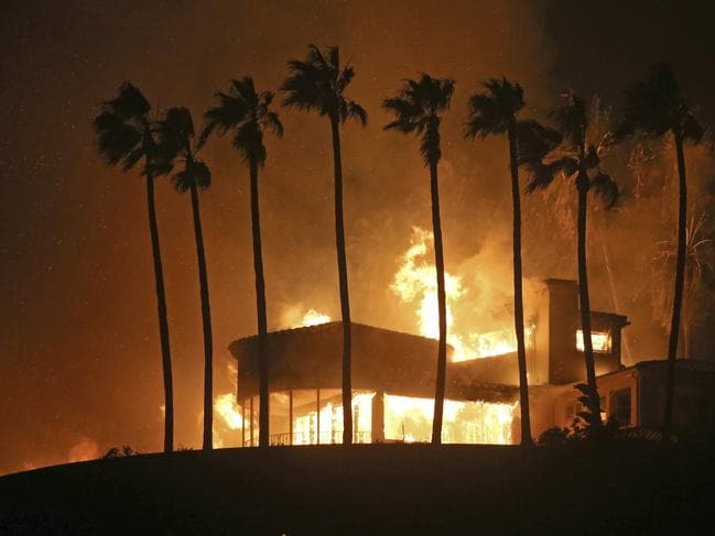 Palm trees frame a home being destroyed by a wildfire above Pacific Coast Highway in Malibu. Picture: AP