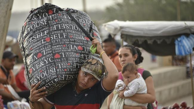 A Venezuelan man carries a large bag on his shoulder with belongings as he crosses the border from Venezuela to Colombia.