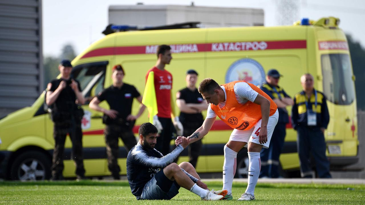 France's forward Nabil Fekir (L) is helped up during the friendly.