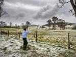 Farmer Dave Richardson stands in his paddocks that now resemble snowfields after being smashed with hail and destructive winds as a super cell storm tore through Long Flat south of Gympie. Photo Lachie Millard