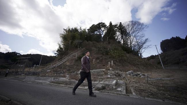 Michihiro Kono walks by a hill where his company's employees ran up to a shrine for safety when the 2011 tsunami hit Rikuzentakata.