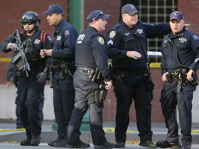 New York Police Department officers gather near the scene. Picture: AP Photo/Bebeto Matthews