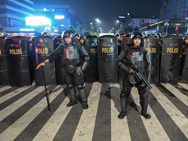 Indonesian police officers stand lined up before dispersing protesters during a demonstration outside the Elections Oversight Body (Bawaslu) in Jakarta. Picture: AFP