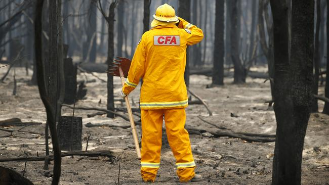 CFA firefighter Lindsay McHugh from South Morang checks smoldering trees in East Gippsland. Picture: David Caird
