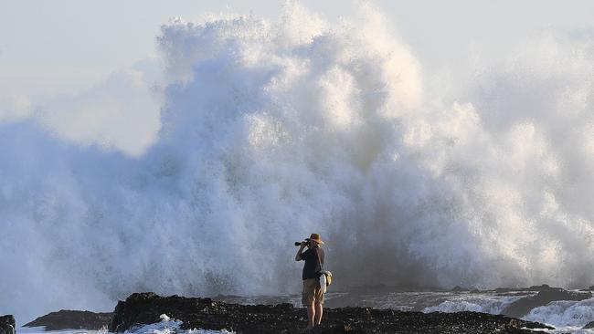 A photographer takes a chance by getting up close to the waves at Snapper Rocks. Picture: AAP Image/Dave Hunt