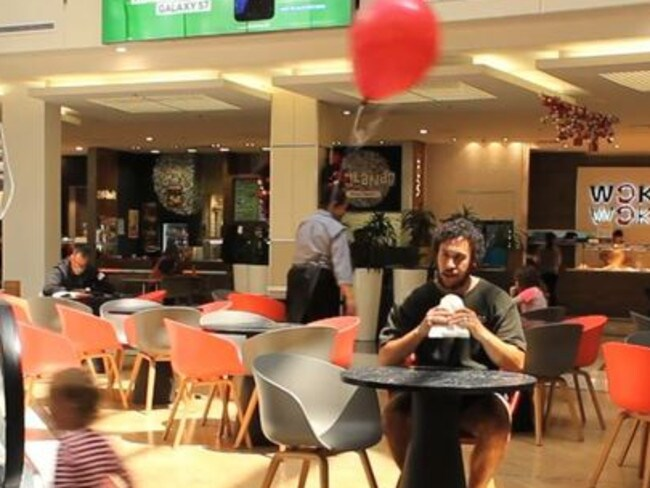 Stress free: Jordan sits and enjoys his meal knowing his daughter (or balloon) is in sight. Picture: YouTube