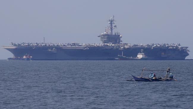Fishermen on board a small boat pass by the USS Carl Vinson aircraft carrier at anchor off Manila, Philippines, for a five-day port call along with guided-missile destroyer USS Michael Murphy. Picture: Bullit Marquez