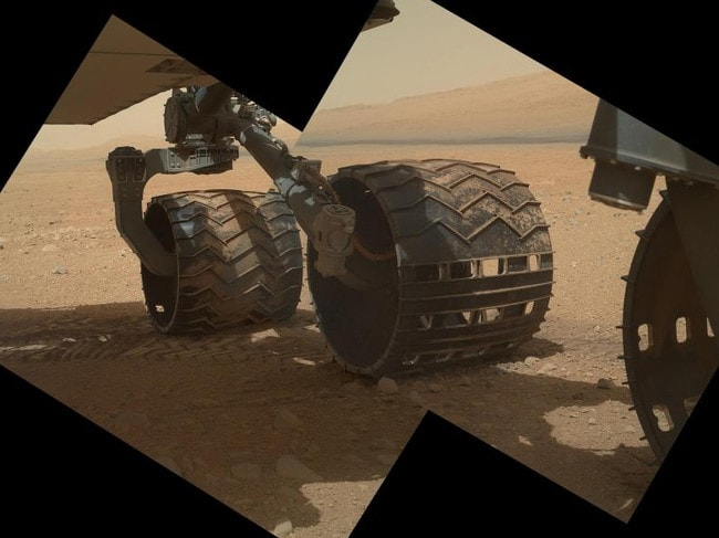 The Curiosity rover took this photo in 2012, showcasing its own three left wheels. In the distance you can see the lower slope of Mount Sharp. Picture: NASA