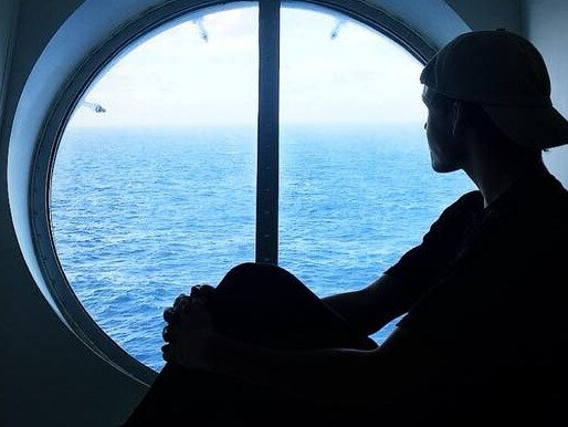Mr Hough gazes through a porthole on board the Harmony of the Seas. Picture: Arron Hough/ Facebook