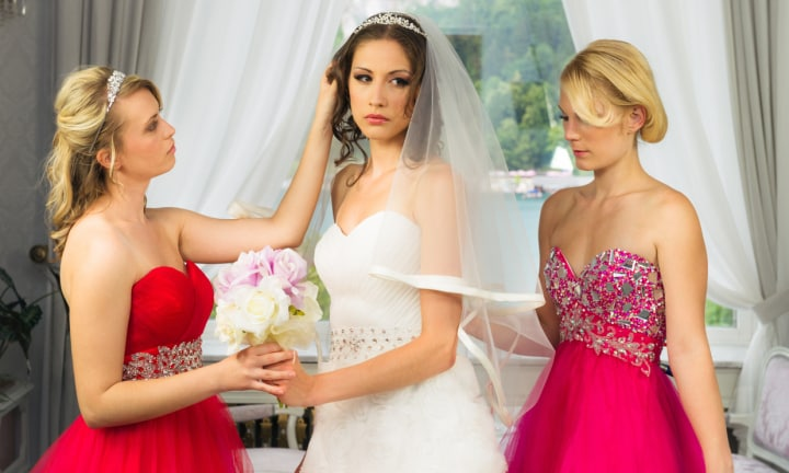 Two bridesmaides helping a nervious bride to finalise her wedding dress and hair, just before the wedding.