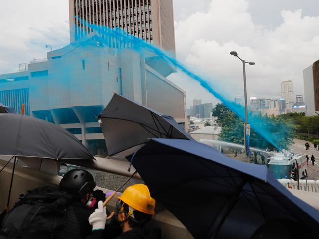 Protesters take cover as policemen fire blue-coloured water on them. Picture: AP/ Kin Cheung