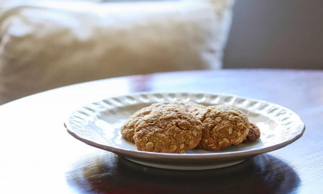 A close up shot of some delicious homemade Anzac biscuits on a white plate.