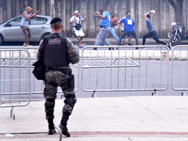 A riot police officer looks at fans of Brazil's Cruzeiro fighting outside the Minerao Stadium.