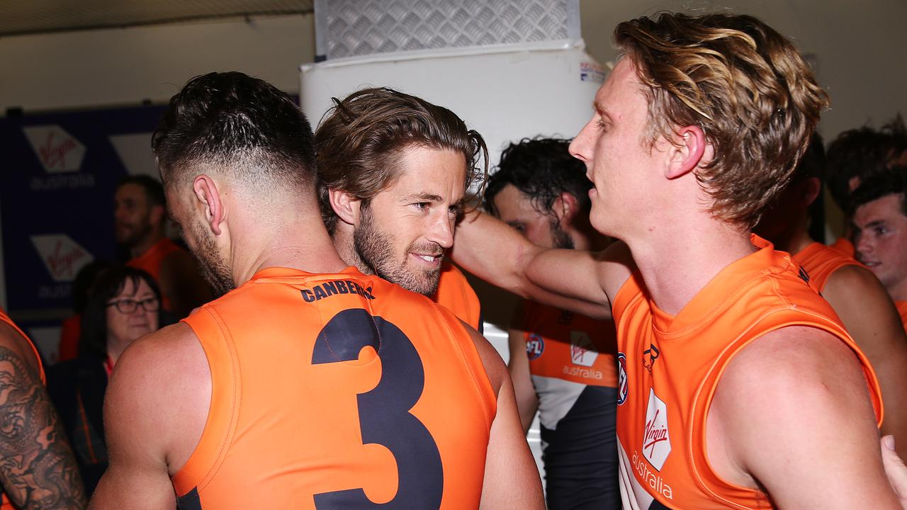 Callan Ward is hugged by Stephen Coniglio and Lachie Whitfield.