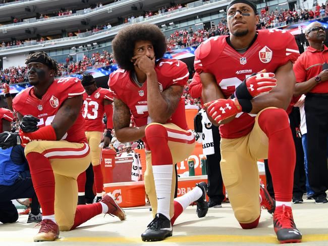 Eli Harold, Colin Kaepernick and Eric Reid of the San Francisco 49ers kneel on the sideline during the US national anthem. Picture: Thearon W Henderson/Getty/AFP