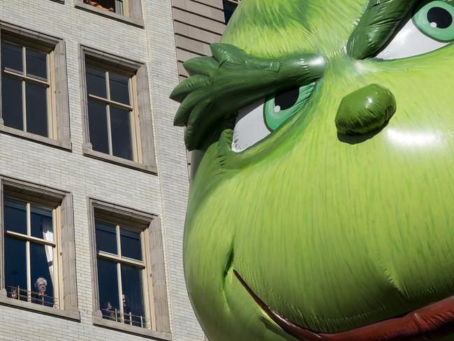 The Grinch balloon passes by windows of a building on Central Park West during Macy's Thanksgiving Day Parade. Picture: AP